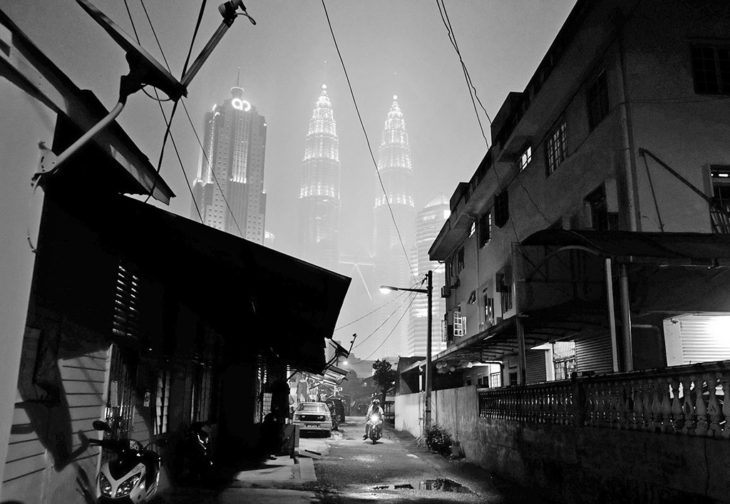 A motorcyclist rides through an alley as Kuala Lumpur's Iconic Petronas Twin Towers stand shrouded in haze in Kuala Lumpur, Malaysia